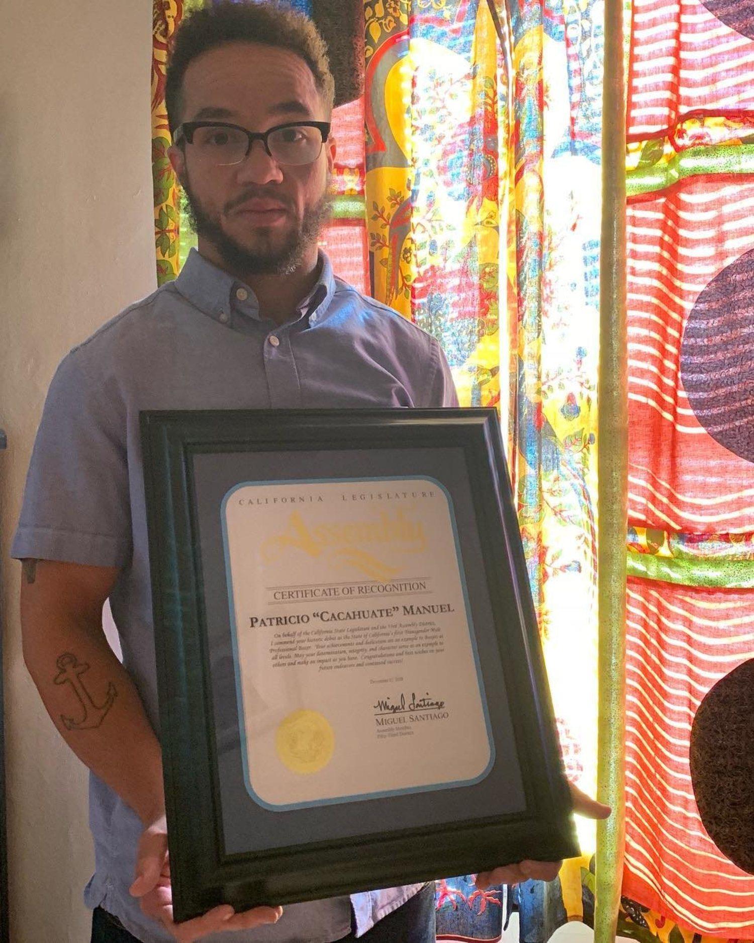 Patrio Manuel sostiene el Certificado de Reconocimiento por su