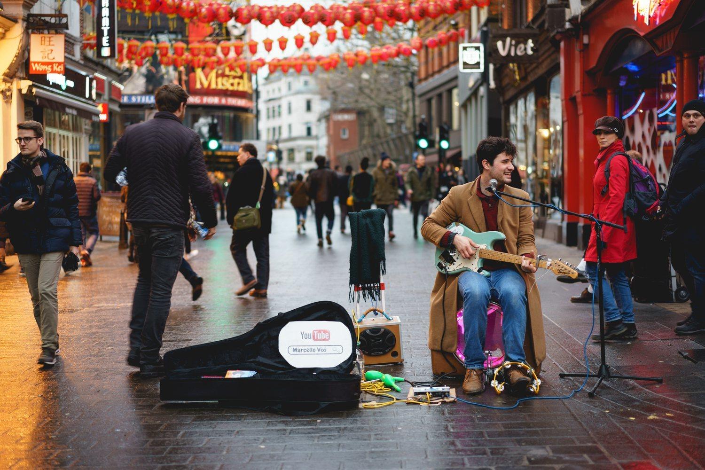 Un músico callejero con un artel que anuncia su canal de Youtube