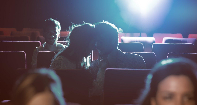 Nótese como el espectador de atrás está siendo molestado por la pareja feliz
