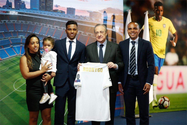 Rodrygo sostiene la camiseta de su nuevo equipo y a la izquierda su hermano,... digo su padre Eric
