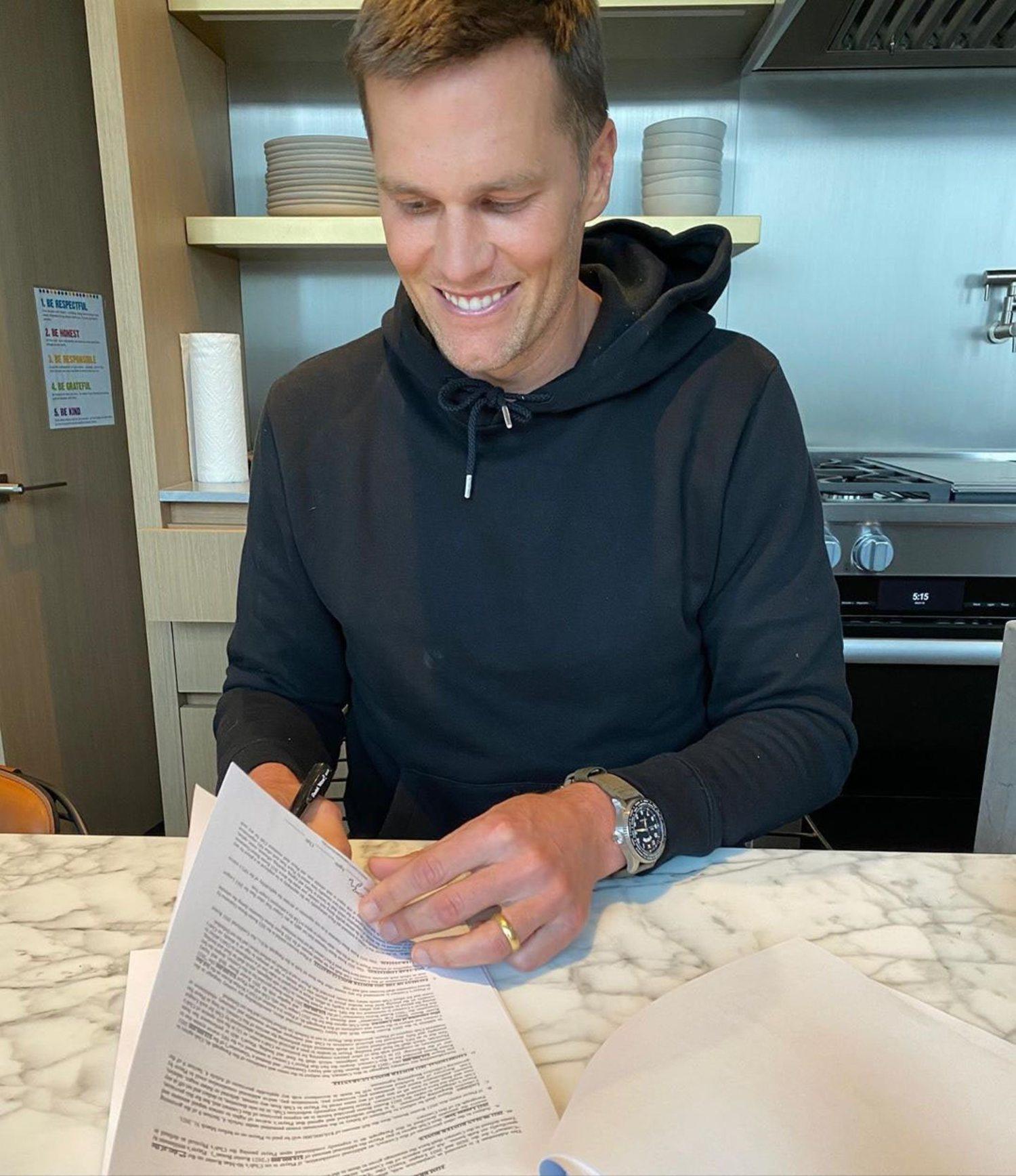 Tom Brady firmando su nuevo contrato con los Tampa Bay Bucaneers.