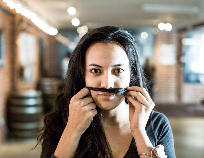 Una 'Mo Sista' imita un bigote con su pelo.