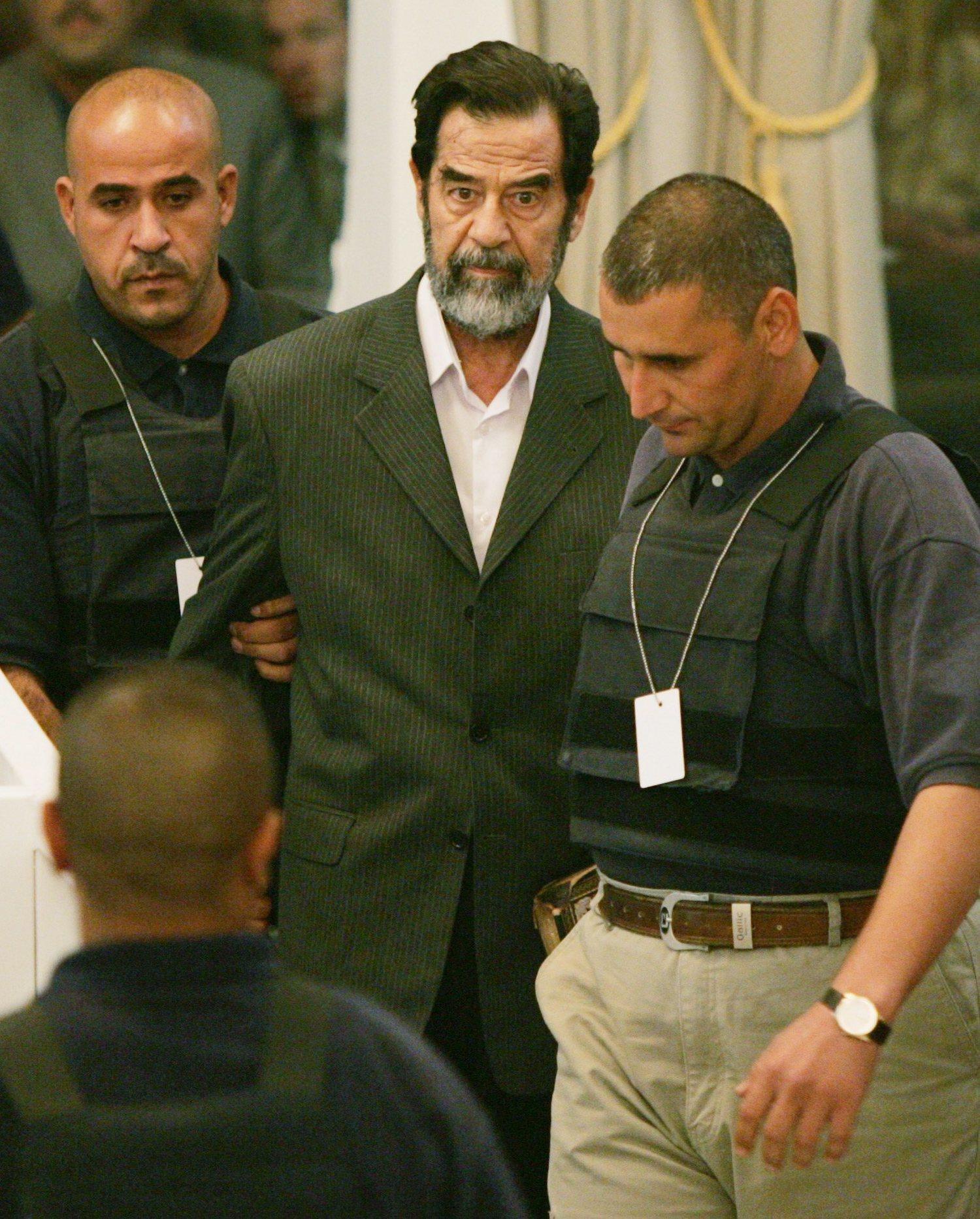 Saddam Hussein junto a dos policías.